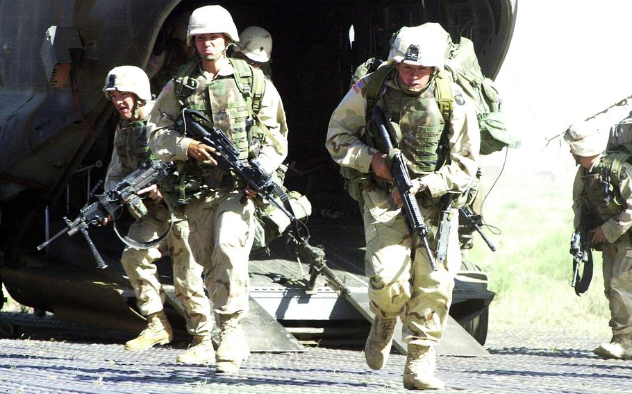 Troops from the 101st Airborne Division in Afghanistan rehearse combat drills at Bagram Airfield in May 2002.