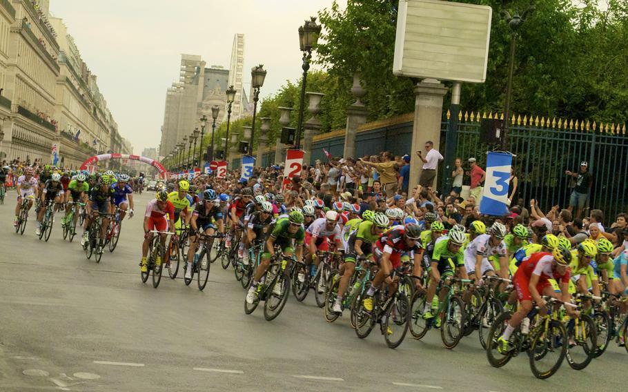 The Tour de France peloton races down the Champs-Élyséesin Paris en route to the finish line.