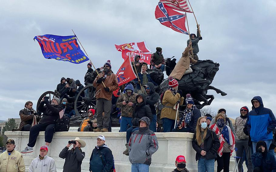 Trump supporters, including one waving a Confederate flag, watch rioters storm the Capitol in Washington, D.C., on Jan. 6, 2021.   Robert Reid/Stars and Stripes