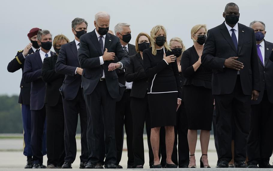 President Joe Biden, first lady Jill Biden and others attend a casualty return as a carry team finishes placing the transfer case containing the remains of Marine Corps Lance Cpl. Jared M. Schmitz, 20, of St. Charles, Mo., into a transfer vehicle on Aug. 29, 2021, at Dover Air Force Base, Del.