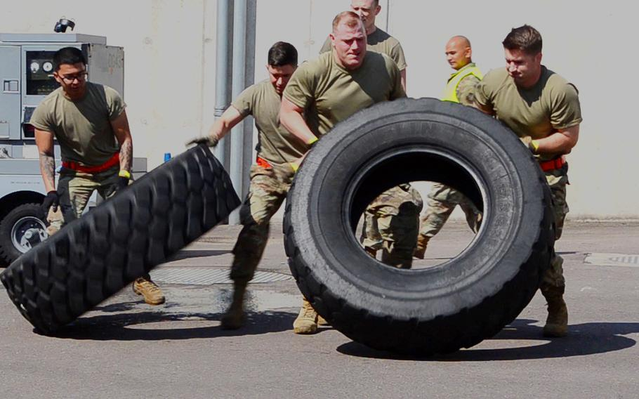 The Raven's Fury team, part of the 726th Air Mobility Squadron out of Spangdahlem Air Base, does the tire flip event during the endurance exercise of the 721st Aerial Port Squadron Multi-Capable Airmen Rodeo at Ramstein Air Base, July 23, 2021. The tire on the left was filled with water to add to the difficulty.