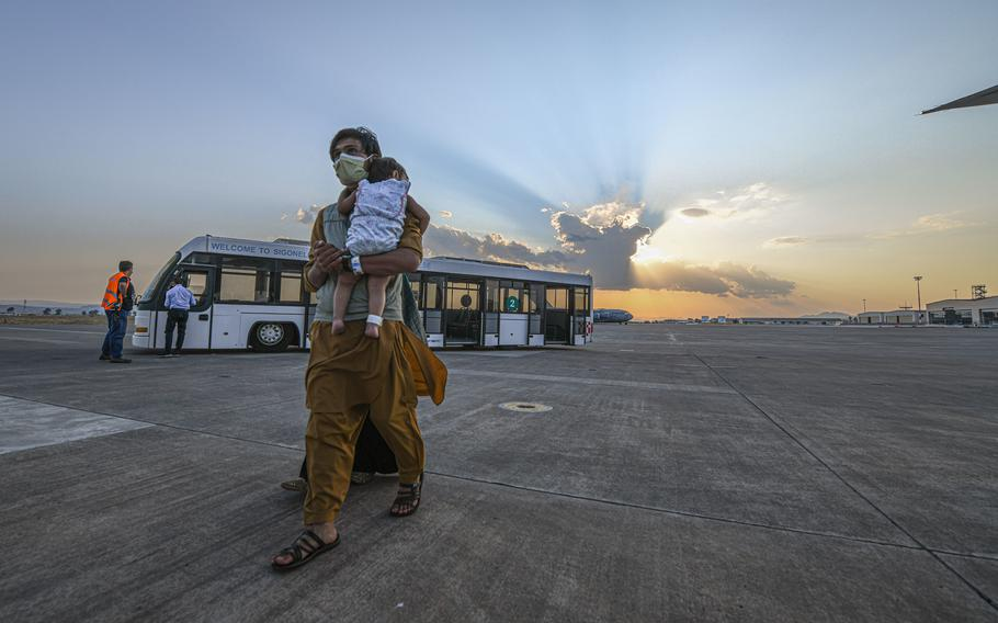 Evacuees from Afghanistan board a Boeing 777 bound for the United States from Naval Air Station Sigonella, Italy, Aug. 28, 2021.