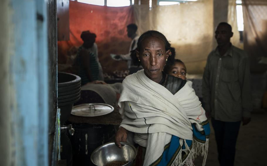 A displaced Tigrayan woman walks out of a classroom-turned-kitchen after receiving food at the Hadnet General Secondary School which has become a makeshift home to thousands displaced by the conflict, in Mekele, in the Tigray region of northern Ethiopia on May 5, 2021.