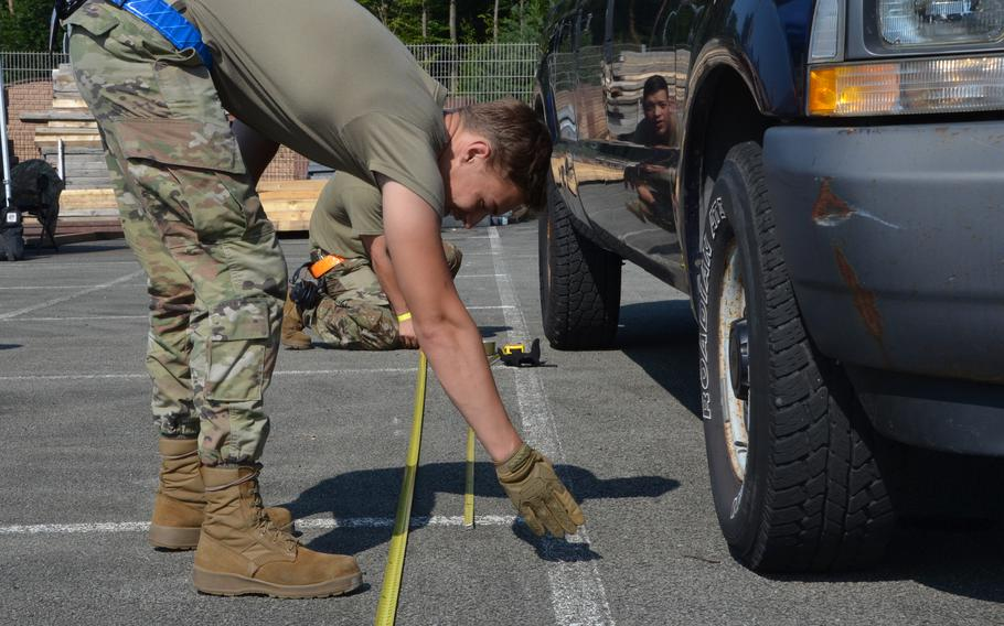 Members of Team PDLC take measurements to calculate the center of balance of a vehicle during the 721st Aerial Port Squadron Multi-Capable Airmen Rodeo at Ramstein Air Base, July 23, 2021.