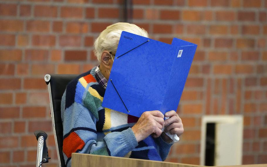 The accused Josef S. covers his face as he sits at the court room in Brandenburg, Germany, Thursday, Oct. 7, 2021. The 100-year-old man charged as an accessory to murder on allegations that he served as a guard at the Nazis' Sachsenhausen concentration camp during World War II.