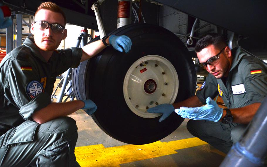 German military academy cadets Tim Herbst, left, and Tom Palzer listen to instructions from U.S. maintainers at Ramstein Air Base before removing the wheels of a C-130J to check the bearings on July 15, 2021. The future Luftwaffe pilots were among seven cadets majoring in aeronautical engineering at the University of the Armed Forces in Munich who did their required practical training at the U.S. air base.
