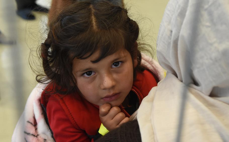A little girl is held while sitting inside a makeshift passenger terminal for evacuees from Afghanistan who are waiting for a flight to the United States from Ramstein Air Base, Germany, Aug. 26, 2021. The number of inbound evacuees is far exceeding the number of outbound passengers.