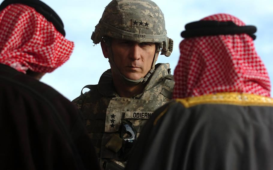 """Lt. Gen. Raymond Odierno, commander of Multi-National Corps-Iraq, speaks with a group of local sheiks at Patrol Base Kemple, Dec. 18, 2007. Odierno, a four-star Army general who was a key architect of the """"surge"""" in U.S. forces during the Iraq War that was credited with reducing violence and increasing stability in the country and who later became the Army's chief of staff, died Oct. 8, 2021, at age 67."""