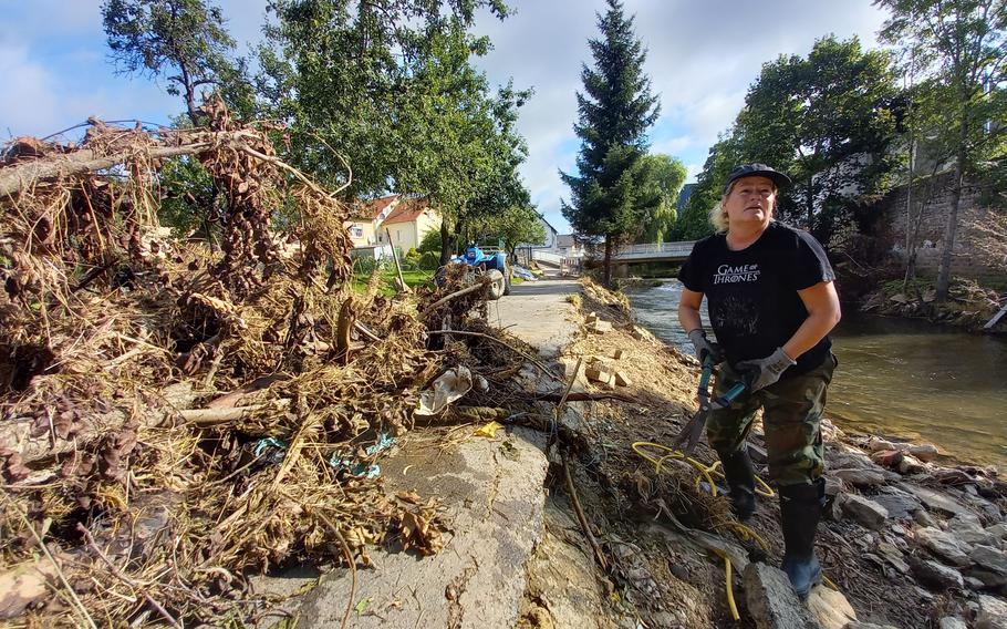 Stephanie Anderons, a German married to a retired American airman, helped clean up parts of the river bank on July 31, 2021, in Rittersdorf, Germany. Western Germany saw some of its worst flooding in decades last month.