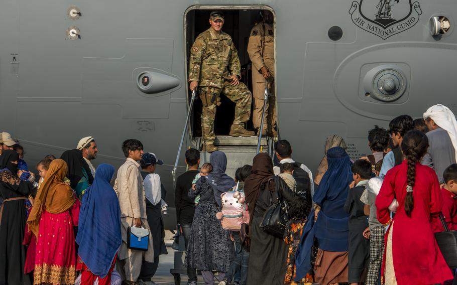 Service members prepare to board Afghan evacuees onto a C-17 Globemaster lll Aug. 22, 2021, at Al Udeid Air Base, Qatar.