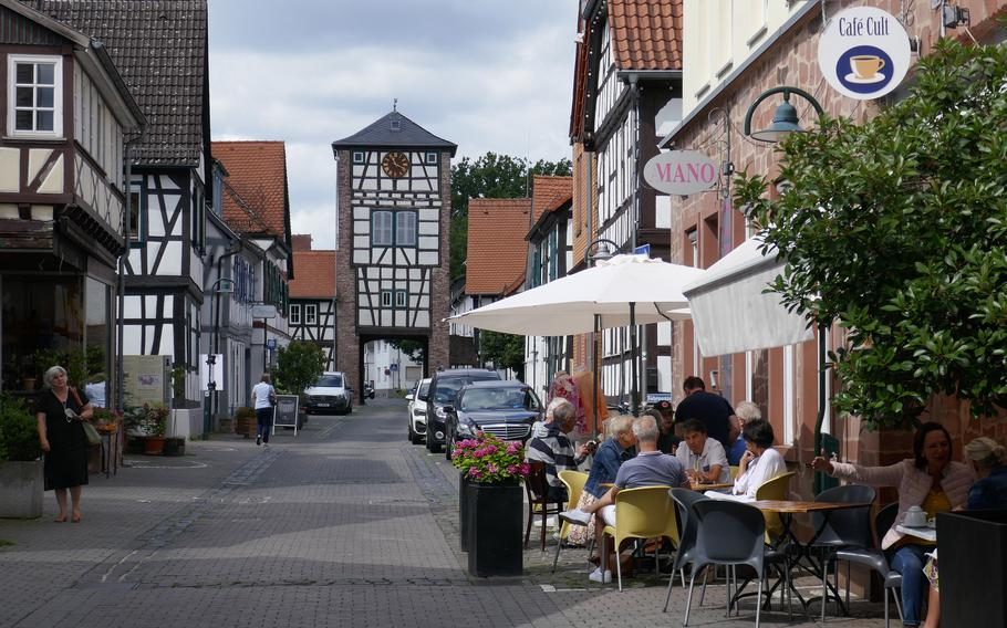 People sit at a cafe on Fahrgasse in Dreieichenhain, Germany. In the background is the Obertor, one of the two tower gates that bookend the street. The town, about 30 miles east of Wiesbaden, is known for its colorful half-timbered houses and its medieval castle.