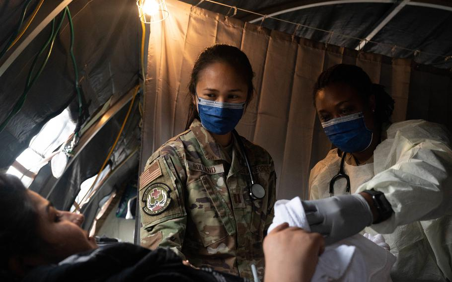 Air Force Capt. Danielle Holland, left, an OB-GYN physician at RAF Lakenheath, United Kingdom, and U.S. Army Lt. Col. L. Rene Key,  director of the Carl R. Darnall Army Medical Center OB-GYN course at Ft. Hood, Texas, provide medical care to an evacuee at Ramstein Air Base, Germany, Aug. 31, 2021. A field hospital and medical tent with OB-GYN care is available for expectant mothers and newborn babies in need of emergency treatment.
