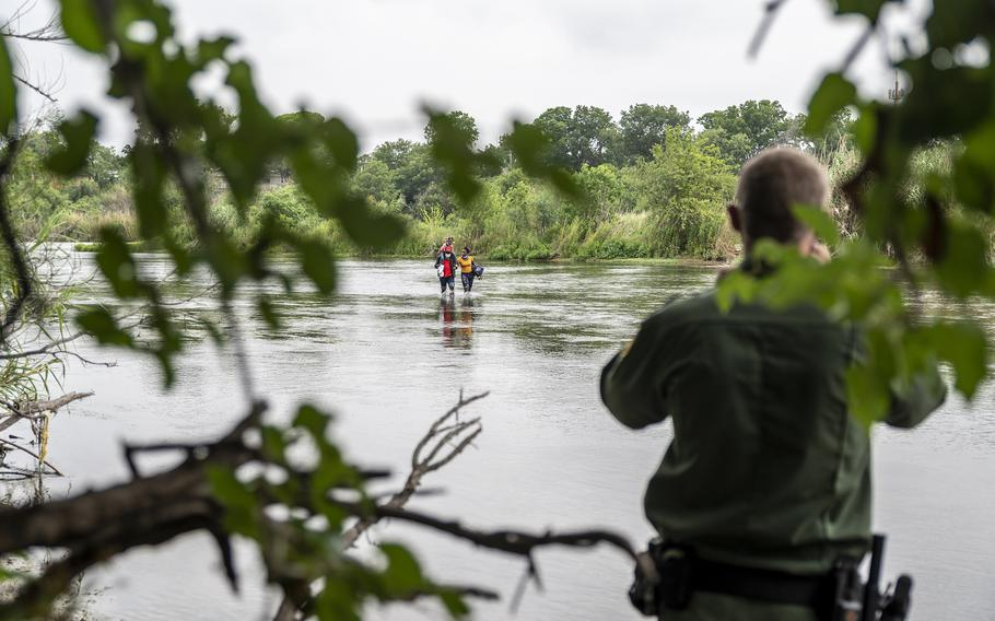A Border Patrol agent watches a Haitian family approach the U.S. side of the Rio Grande on June 25 in Del Rio, Texas. MUST CREDIT: Photo for The Washington Post by Sergio Flores