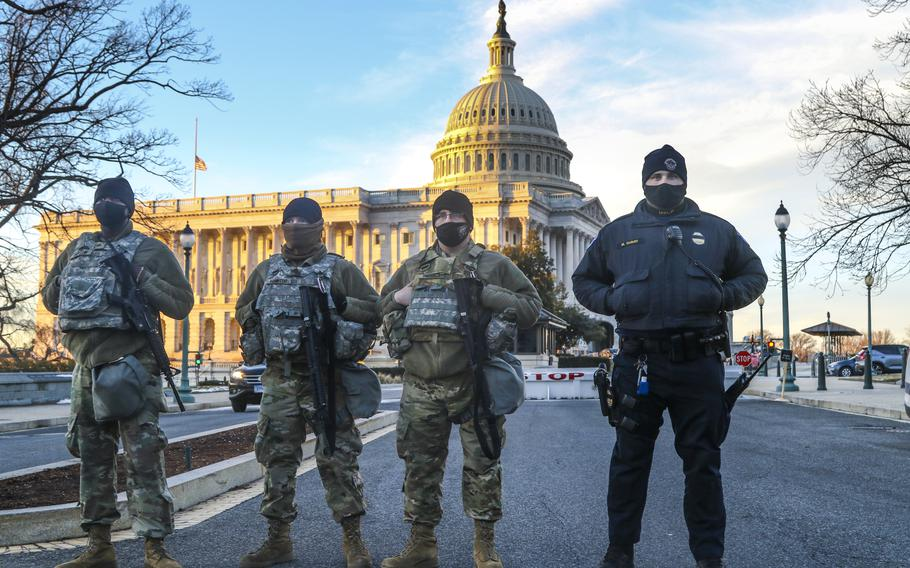 From left: U.S Army Sgt. Gio Carter, Sgt. Aaron Hampton, and Pvt. Cody Harrison, all with Forward Support Company 507th Engineer Battalion, Michigan National Guard, provide security with U.S. Capitol Police officer Mitchell Dunay, near Capitol Hill in Washington, D.C., on Feb. 3, 2021.
