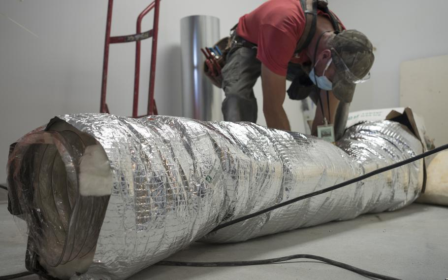 A worker installs a negative air pressure HVAC system during construction for pharmacy area expansion at Katherine Shaw Bethea Hospital in Dixon, Ill., on August 24, 2021.