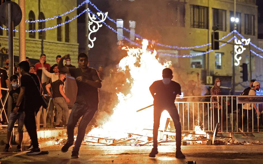Palestinian protesters hurl stones at Israeli security forces amid clashes in Jerusalem's Old City on Saturday, May 8, 2021.