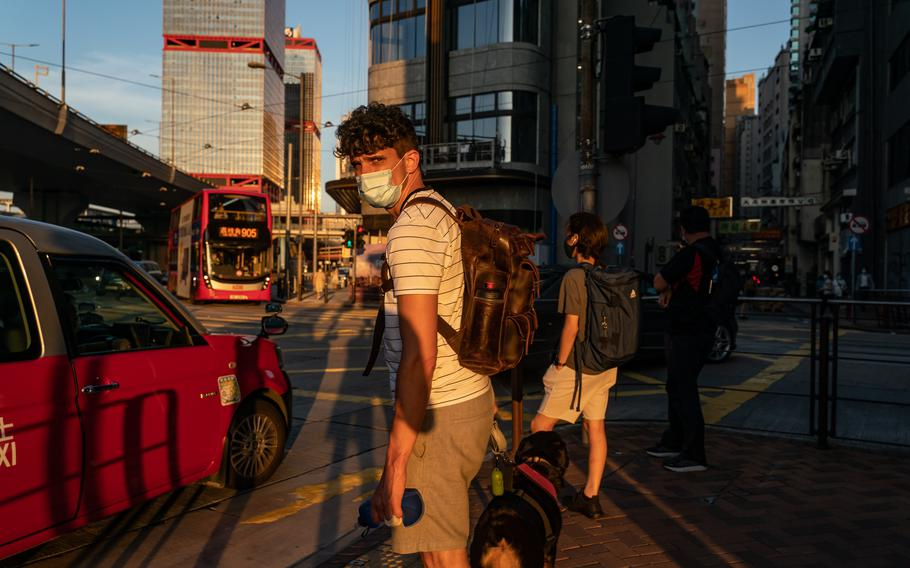 Samuel Phillip Bickett walks his dog, Mui Mui, on Aug. 17, 2021, in Hong Kong. The corporate lawyer was convicted and jailed for assaulting an officer.