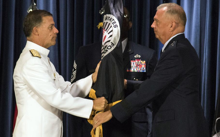 Adm. John Aquilino, the head of Indo-Pacific Command, passes the guidon to the new commander of U.S. Forces Japan and 5th Air Force, Lt. Gen. Ricky Rupp, at Yokota Air Base, Japan, Friday, Aug. 27, 2021.