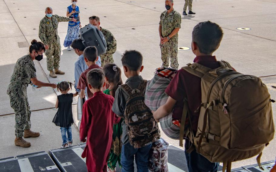 Sailors stationed at Naval Station Rota, Spain, greet evacuees from Afghanistan after their arrival at the base aboard a U.S. Air Force C-17 Globemaster III, Sep. 1, 2021.