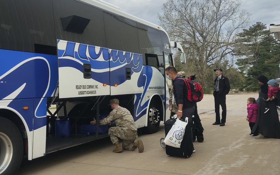 Soldiers help Afghan families load their luggage on a bus out of Fort McCoy, Wis., Oct. 11, 2021. They were among the first to leave the base and begin the journeys to their new hometowns.