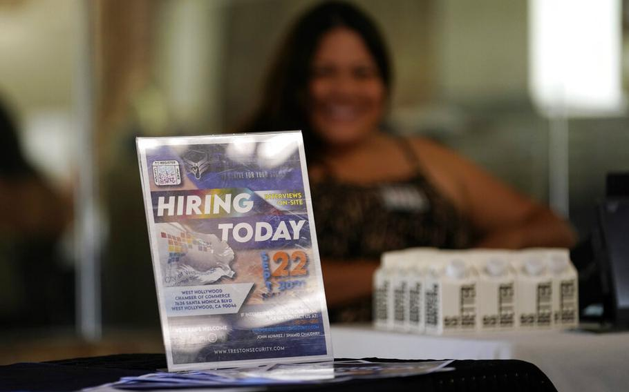 A hiring sign is placed at a booth for prospective employers during a job fair Wednesday, Sept. 22, 2021, in the West Hollywood section of Los Angeles.  The number of Americans applying for unemployment aid rose last week for a second straight week to 351,000, a sign that the delta variant of the coronavirus may be disrupting the job market's recovery, at least temporarily.