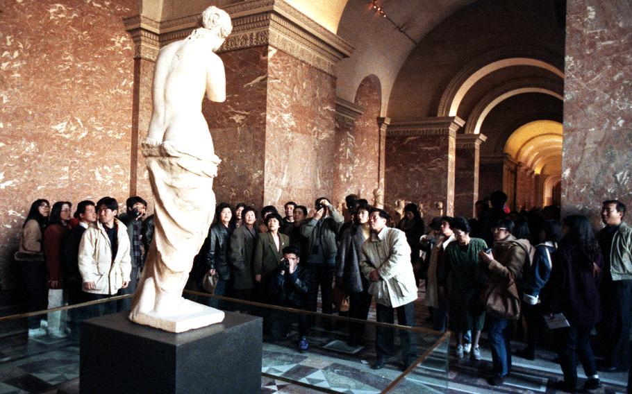 Tourists gather around the Venus de Milo at the Louvre in Paris.