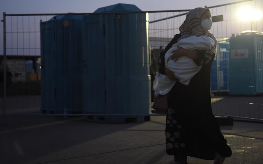 An Afghan woman clutches her baby before preparing to depart on a flight from Ramstein Air Base, Germany, to the United States, Sept. 2, 2021. So far more than 22,000 evacuees from Afghanistan have flown through Ramstein to the United States or other destinations.