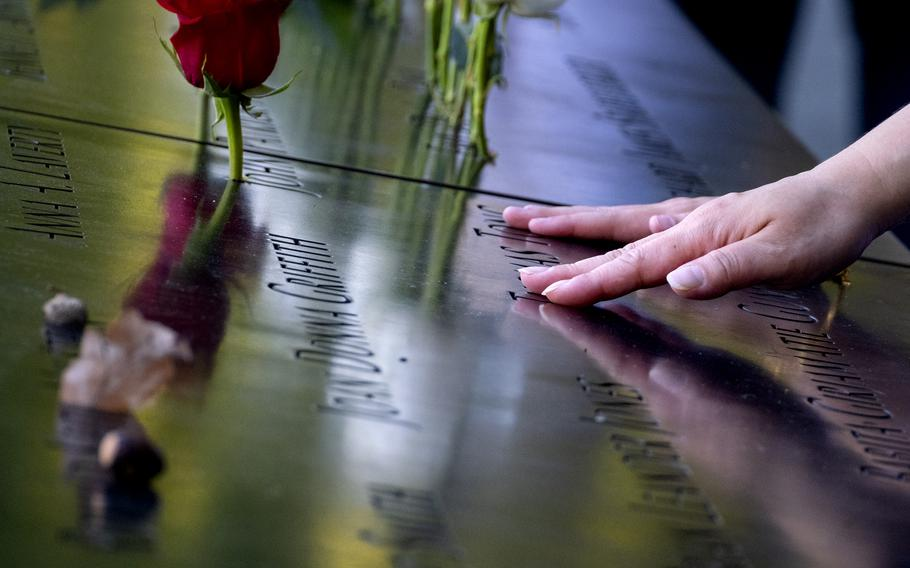 Hands touch the names of people who were killed during the attacks on the World Trade Center on Sept. 11, 2001, as families gather at the National September 11 Memorial in New York on the 20th anniversary of the attacks, Saturday, Sept. 11, 2021.