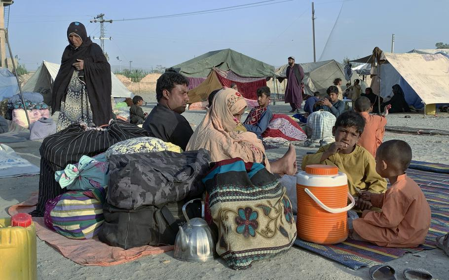 Afghan families sit outside their tents in an open area on the outskirts of Chaman, a border town in the Pakistan's southwestern Baluchistan province, Tuesday, August 31, 2021.