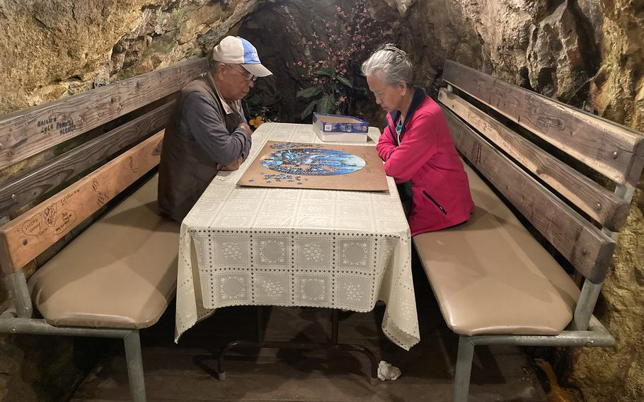 Hak (left) and Ung Shin spend time in a tunnel at the Merry Widow Health Mine in Basin, Montana, on June 30, 2021 piecing together a puzzle. For more than a decade, the California couple have made the trip to expose themselves to radioactive radon, which they say keeps them healthy.