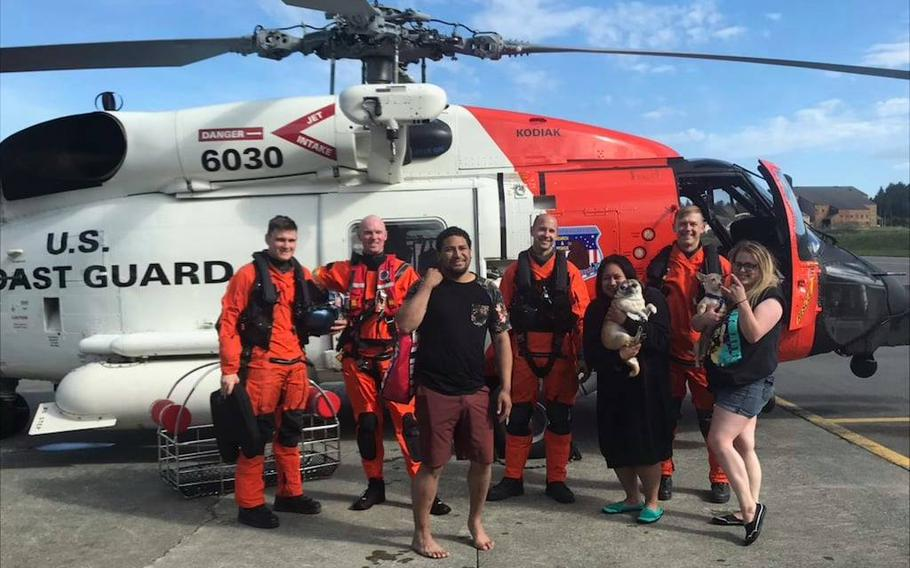 Members of the Alaska's U.S. Coast Guard Air Station in Kodiak rescued Nation Sega, left, Lepa Sega, middle, and Hollie Spence (and their pups) on Saturday after their pink flamingo raft was swept across Monashka Bay.
