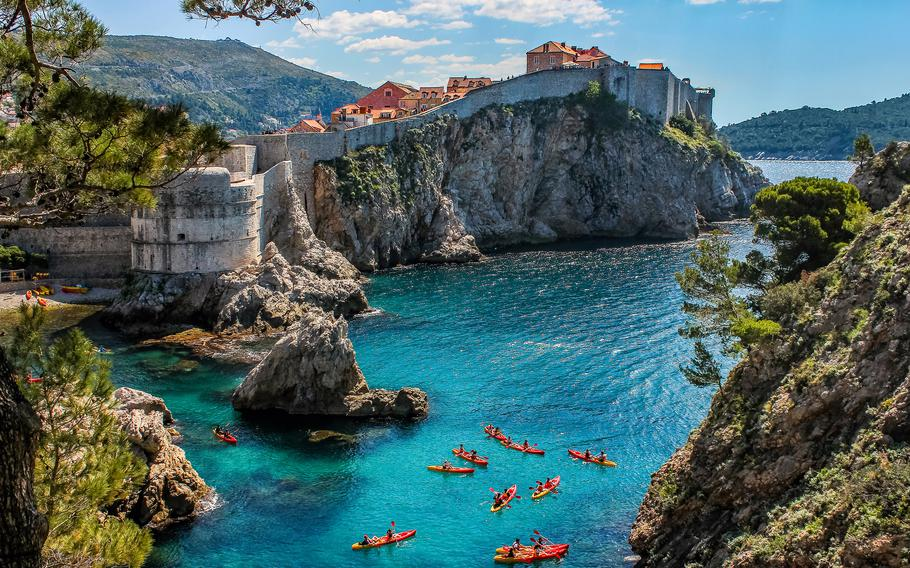 Kayakers paddle through the crystal-clear blue water below the walls surrounding Dubrovnik, Croatia.