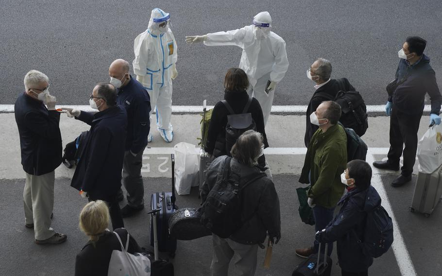 """In this Jan. 14, 2021, file photo, a worker in protective coverings directs members of the World Health Organization (WHO) team on their arrival at the airport in Wuhan in central China's Hubei province. China's Foreign Ministry on Thursday, Oct. 14, warned against what it called possible """"political manipulation"""" of a renewed probe by the World Health Organization into the origins of the coronavirus, while saying it would support the international body's efforts."""