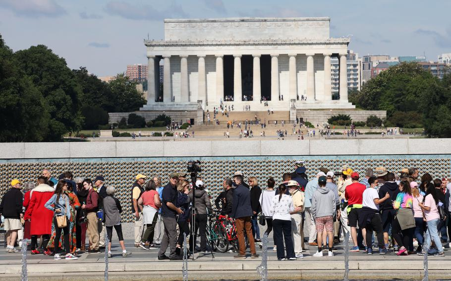 With the Lincoln Memorial as a backdrop, members of the public meet participants in a Memorial Day ceremony at the National World War II Memorial in Washington, D.C., May 31, 2021.