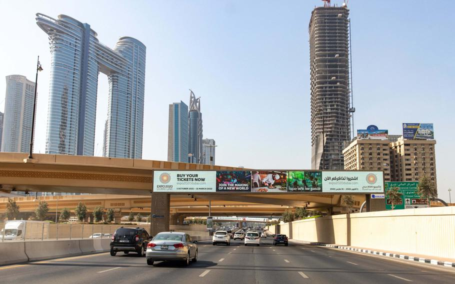 Motorists drive under a digital advert for Expo 2020 Duabi on Sheikh Zayed Road in downtown Dubai, United Arab Emirates, on Sept. 28, 2021.