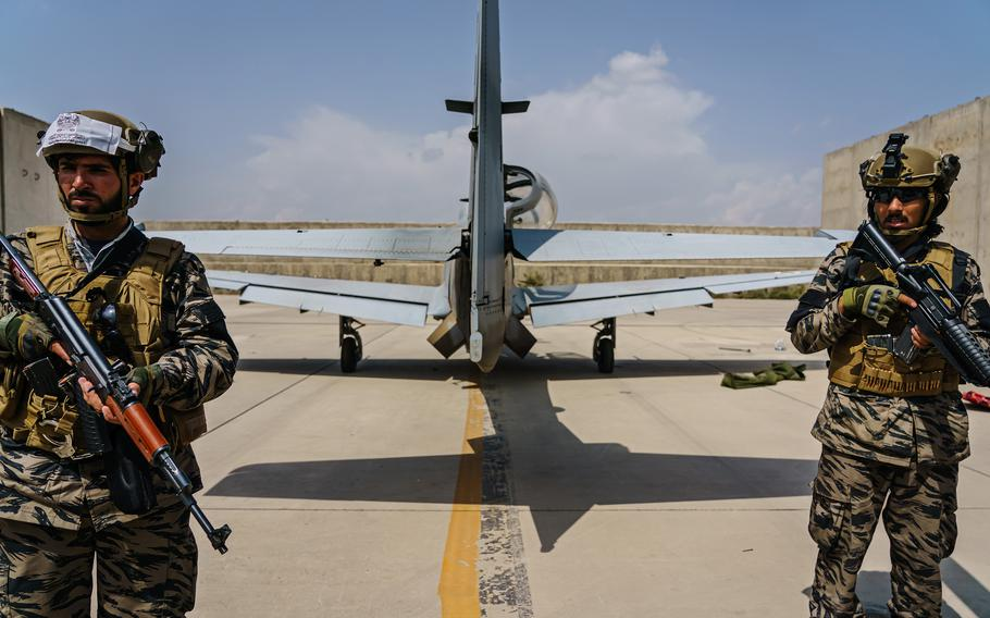 Taliban fighters stand guard behind an airplane left by U.S. forces at Hamid Karzai International Airport in Kabul, Afghanistan, Tuesday, August 31, 2021.