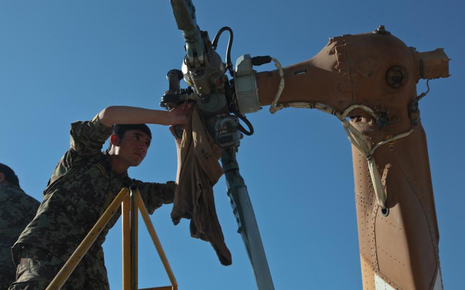 An Afghan army air corps soldier cleans the rear rotor of an Mi-17 helicopter during aircraft maintenance in Afghanistan in 2012. The forces have since acquired U.S.-made Black Hawk helicopters. Afghan maintainers said theyve been practicing remote assistance via video calls for two months, as U.S-funded maintenance contractors prepare to leave the country.