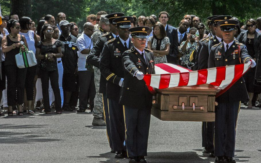 In this July 10, 2008, file photo, friends and family watch a military honor guard carry the casket of Sgt. 1st Class Joseph A. McKay, during a funeral service at Long Island National cemetery in Farmingdale, N.Y.