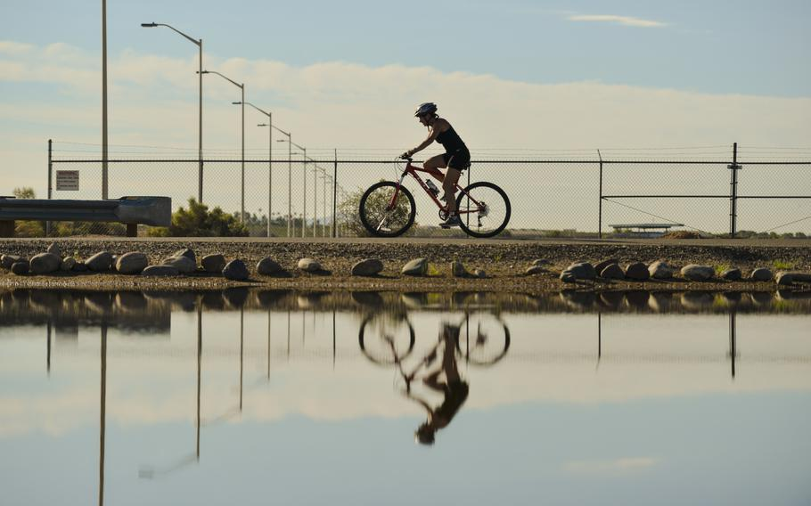 A pool of water reflects a triathlete riding a bike at Luke Air Force Base, Ariz., on Aug. 19, 2017.