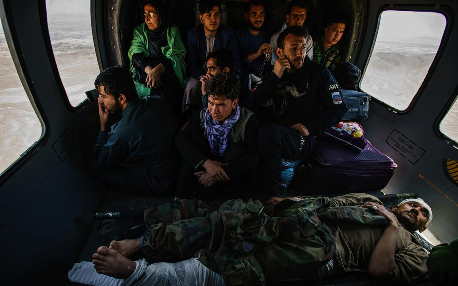 Hosy Andar, deputy governor of Ghazni province, top left, and soldiers, some wounded, are transported from at an outpost in Ghazni Province to Kabul Airbase in Afghanistan. Taliban road closures mean nearly all logistical support to thousands of outposts, including resupplies of ammunition and food, must be done by air.