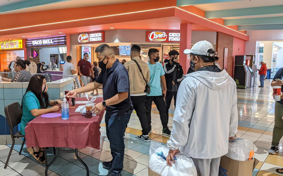 Diners show off their vaccination records and registered phone numbers before entering the Micronesia Mall food court on August 30, the day Guam reinstated a mask warrant and social distancing rules for indoor locations .