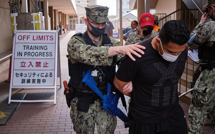 Petty Officer 1st Class James Eggers detains an actor playing an armed suspect during the Citadel Pacific exercise outside the exchange at Yokosuka Naval Base, Japan, July 20, 2021.