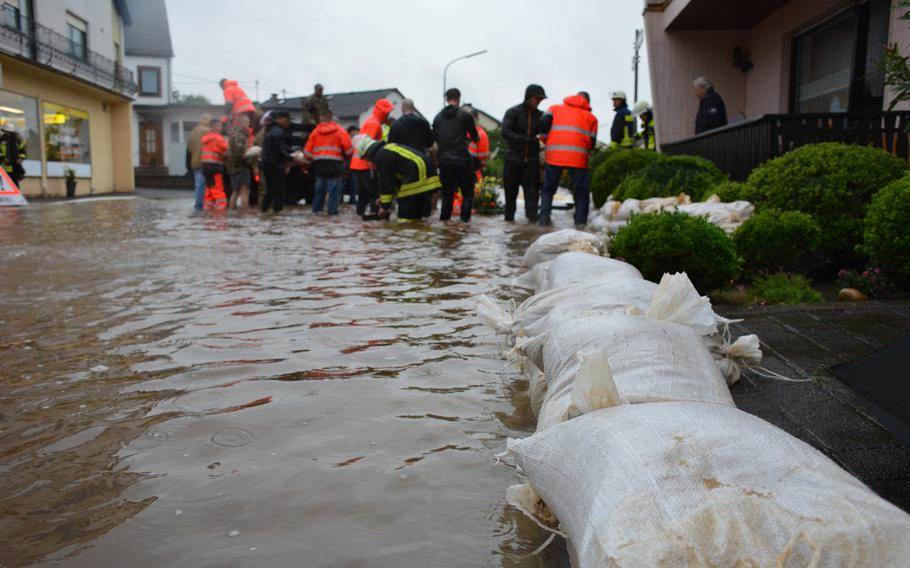 Members of Spangdahlem Air Base's 52nd Civil Engineering Squadron work with German first responders to fill and lay sandbags to prevent flooding in Binsfeld, Germany, July 14, 2021. About 20 military families at Spangdahlem were displaced by the floods and are being housed in temporary lodging on base.