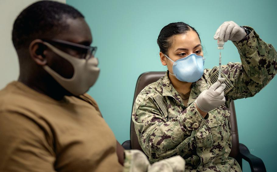 Petty Officer 2nd Class Amanda Reyna prepares to administer a COVID-19 vaccine in spring 2021 in Bahrain.