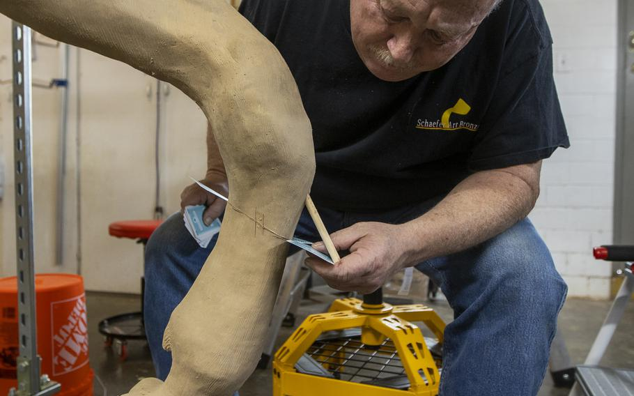 Tommy Ladd, owner of Schaefer Art Bronze Casting, uses playing cards to mark the areas where the statue will be cut and molded. The statue is taken apart before being cast in bronze at the foundry.