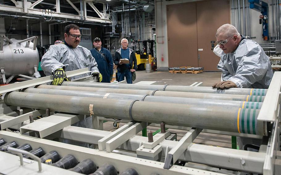 Blue Grass Chemical Agent-Destruction Pilot Plant operators place the first M55 rockets containing VX nerve agent on a conveyor to begin the destruction process July 9, 2021.