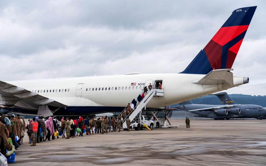 Airmen assigned to the 721st Aerial Port Squadron form a gate Aug. 30, 2021, as evacuees from Afghanistan board a flight at Ramstein Air Base, Germany. An official at Ramstein said flights carrying Afghan refugees from Germany to the U.S. are expected to resume over the Columbus Day weekend. A weekslong pause in flights was imposed after several evacuees were diagnosed with measles.
