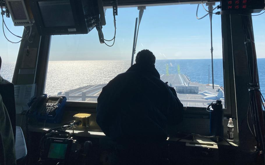 High up on USS Gerald R. Ford's island, controllers in the carrier's primary flight control are just some of the dozens of eyes watching for hazards as pilots take off and land every minute or so, working on their carrier qualifications.
