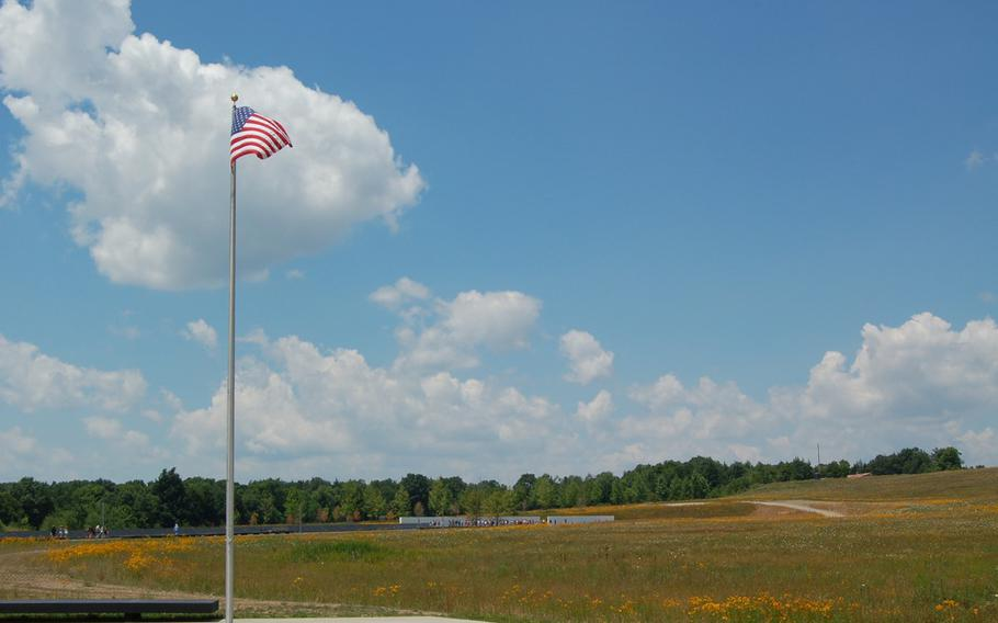 The American flag flies at the Memorial Plaza at the Flight 93 National Memorial with the Wall of Names in the distance. A nonprofit has launched a campaign to develop Patriot Park, a tribute to service members who have given their lives during the global war on terrorism, within the park's boundaries.