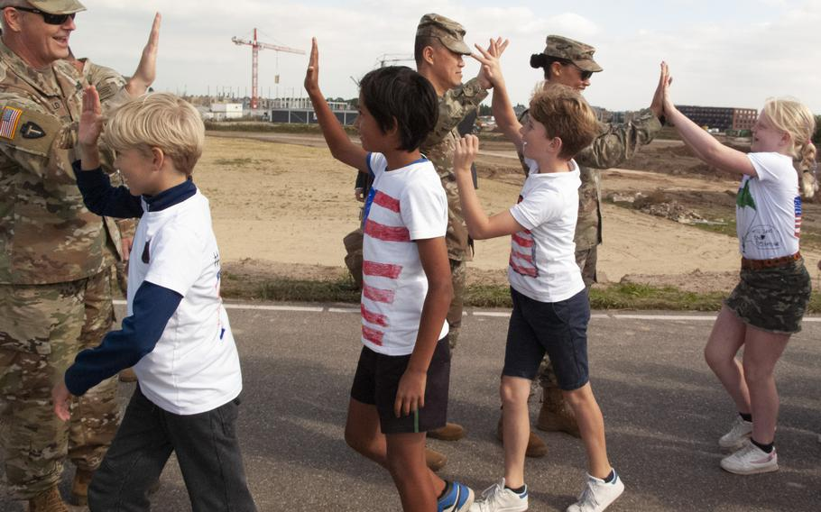 From left to right, Maj. Mark Fitzgerald, Capt. Bau Phan and Lt. Col. Kimberly Baird of the Texas National Guard high-five Dutch children as they arrive to take part in a ceremony in Nijmegen, Netherlands, on Sept. 20, 2021, to remember the crossing of the Waal River by U.S. soldiers 77 years earlier.